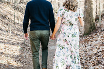 a couple holding hands walking in the woods