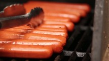 Tongs moving hot dogs on a grill.