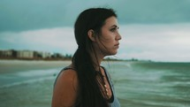 concerned girl standing on a beach