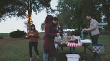 people getting food around a picnic table outdoors