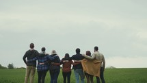group with arounds around each other walking through a field