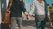 man and woman walking down a sidewalk