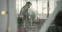 a woman putting potting soil into clay pots in a greenhouse