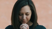 slow motion of a woman bowing in prayer