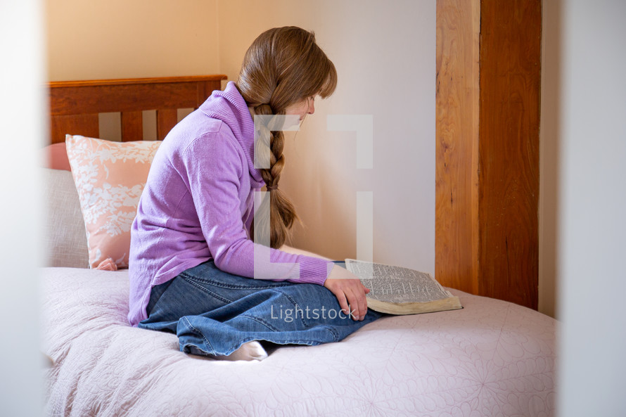 teen girl sitting on the edge of her bed praying over a Bible in her lap