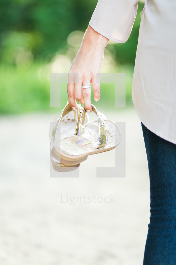 woman carrying her sandals