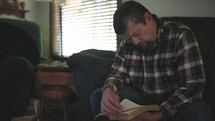 a man praying and reading a Bible