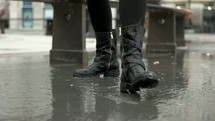 woman in boots splashing in a puddle