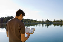 Man reading Bible while standing by a lake.