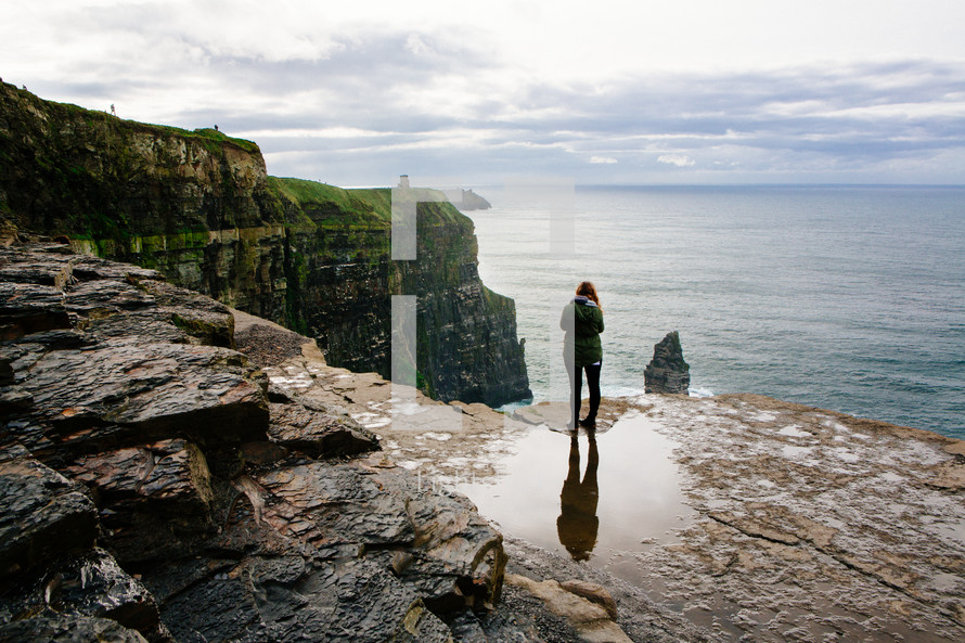 a woman standing on the edge of a cliff