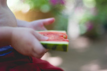 toddler holding a slice of watermelon