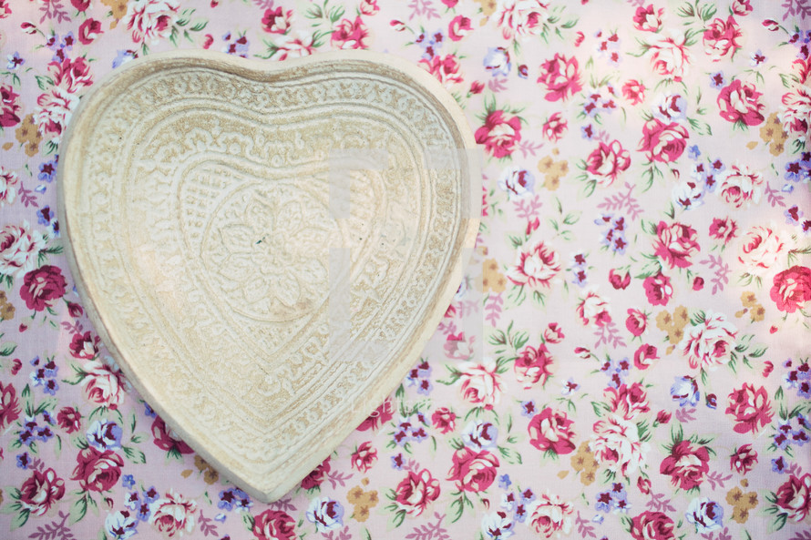 heart shaped plate on floral wallpaper