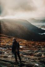 a woman exploring foggy mountaintops
