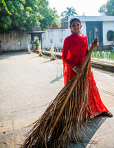 a woman sweeping with a palm frond in India