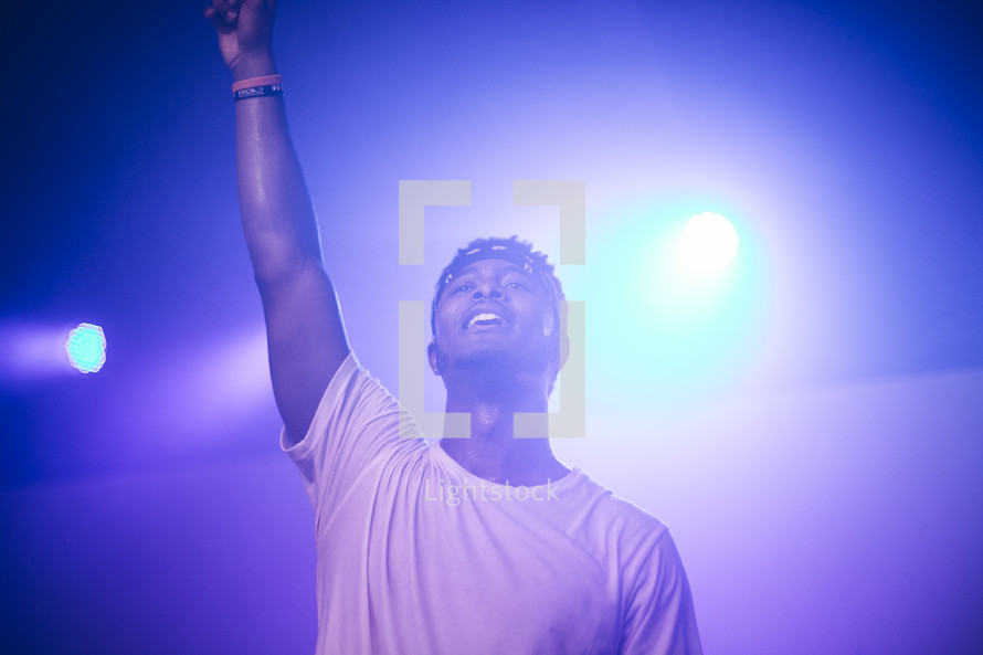 singing, microphone, on stage, man, raised hand, singer, musician, African American, fog machine