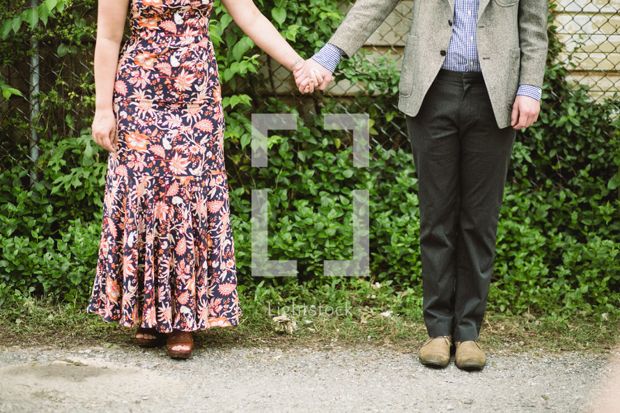 a couple standing outdoors holding hands
