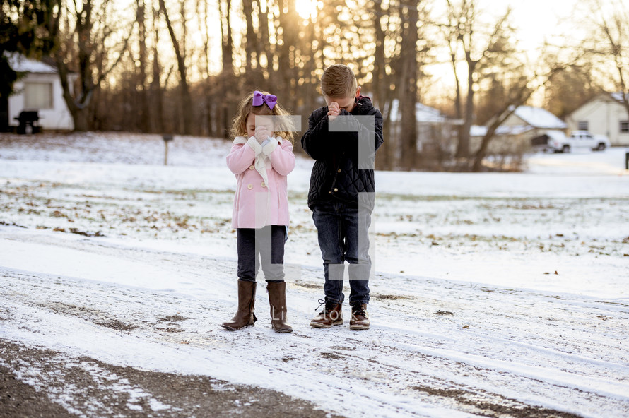 girl and boy child praying outdoors in snow