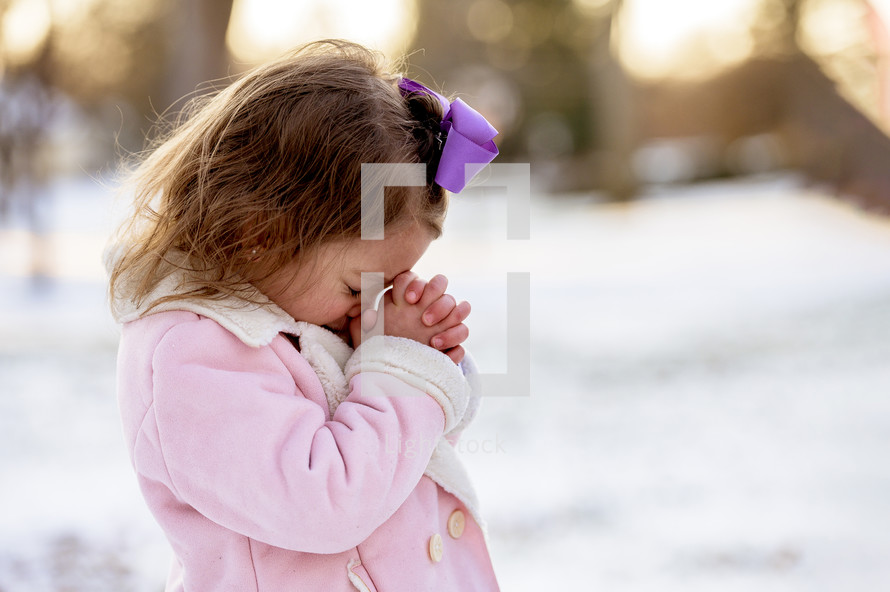 girl child praying outdoors in snow