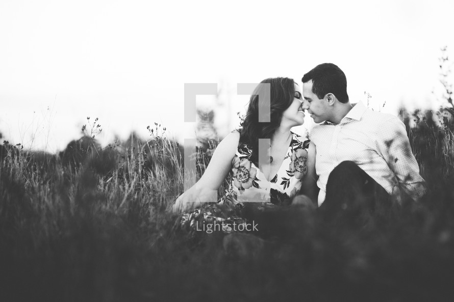 a couple kissing sitting in the grass