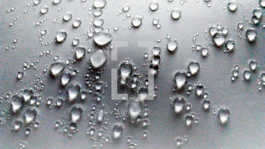 Water droplets appearing on a flat surface after cold and warm air mix and condensation appears on windows and surfaces from cold temperatures warming up due to climate change, weather, storms and ice defrosting.