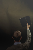 a preacher holding up a Bible during his sermon