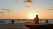 a man sitting on a dock at sunset