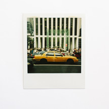 polaroid photograph of a taxi cab in a city