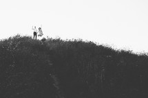 a couple on a hilltop jumping up