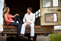 Happy couple sitting on back of abandoned bus