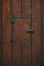 Wooden confessional door with closed priests's window.