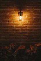 Patio light on brick wall over stack of firewood.