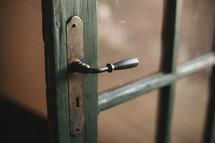 Door with glass panes and antique handle.