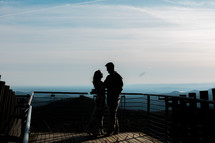 a couple standing on a balcony overlooking a mountain