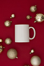 gold Christmas ornaments on a red background and mug