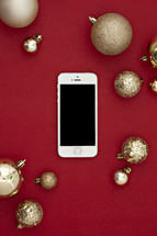 gold Christmas ornaments on a red background and cellphone