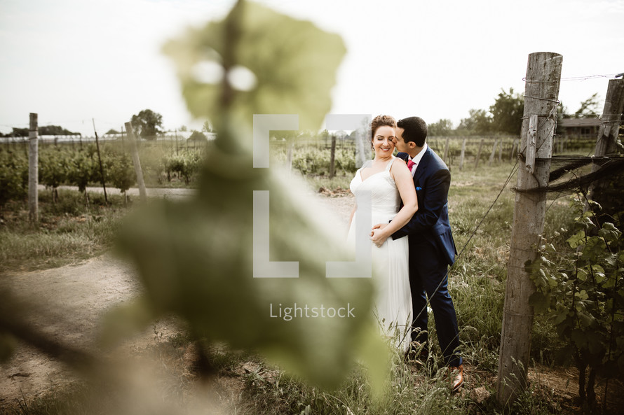 a bride and groom standing in a vineyard