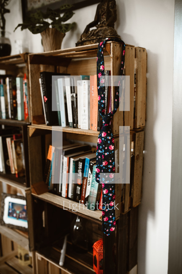 floral tie hanging on a book shelf