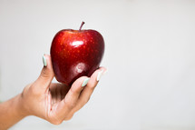 female hand offering a red apple