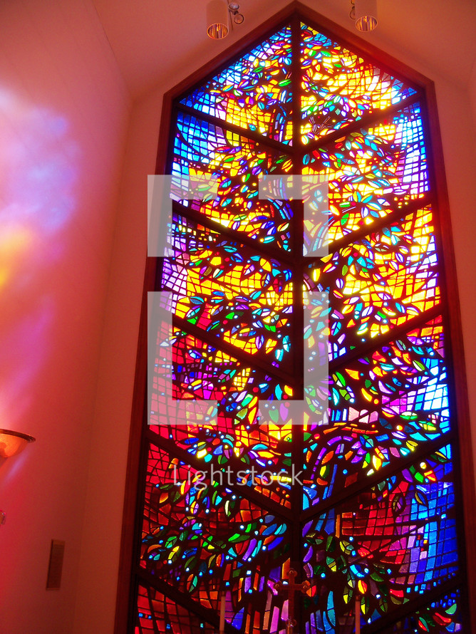 A large stained glass window called The Window to Heaven fills a chapel with warmth and glowing light as church members come in to pray and have quiet time before the Lord.