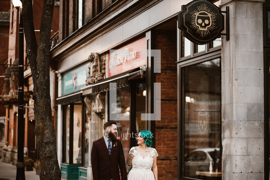 bride and groom standing on a downtown sidewalk