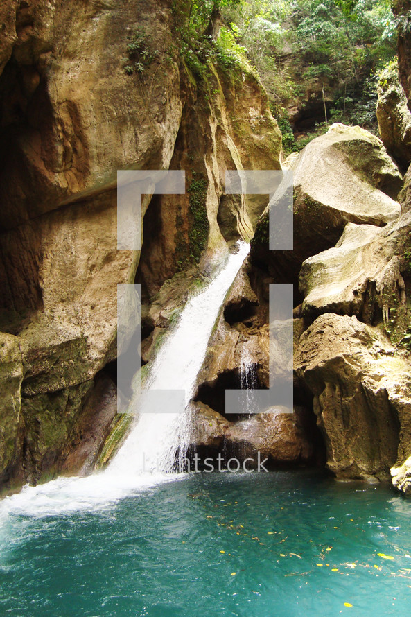 A waterfall feeding into a secluded pool