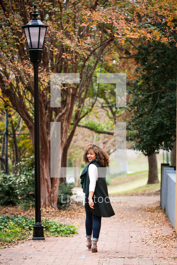 young woman walking on a sidewalk in fall