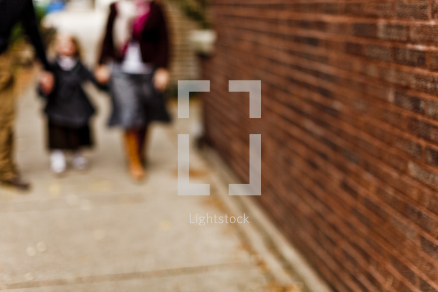 blurry image of people walking on a sidewalk