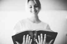 woman smiling reading a Bible