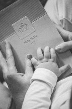 mother and infants hands on a Bible