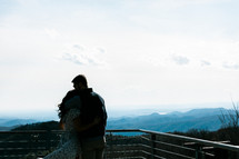 a couple standing on a balcony hugging
