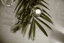 votive candle on palm fronds on a table