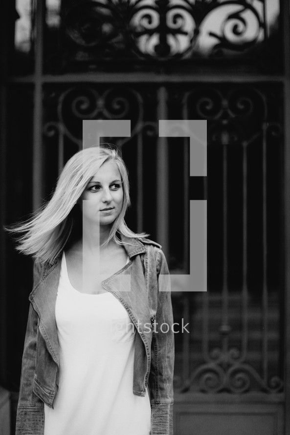 blonde woman with her hair blowing standing in front of a gate