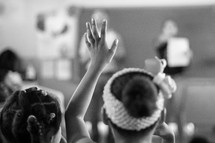 Black and white photograph of little girls at school with hands raised.