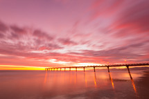 bridge over water under a pink sky at sunset